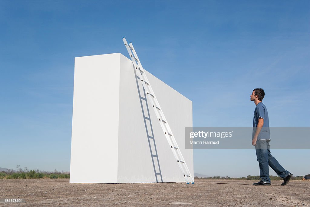 Man looking at ladder against wall outdoors : Stock Photo