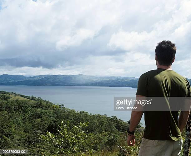 Man looking at lake, rear view