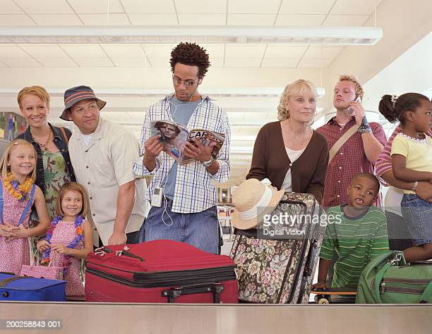 Man looking at magazine waiting at luggage carousel in airport