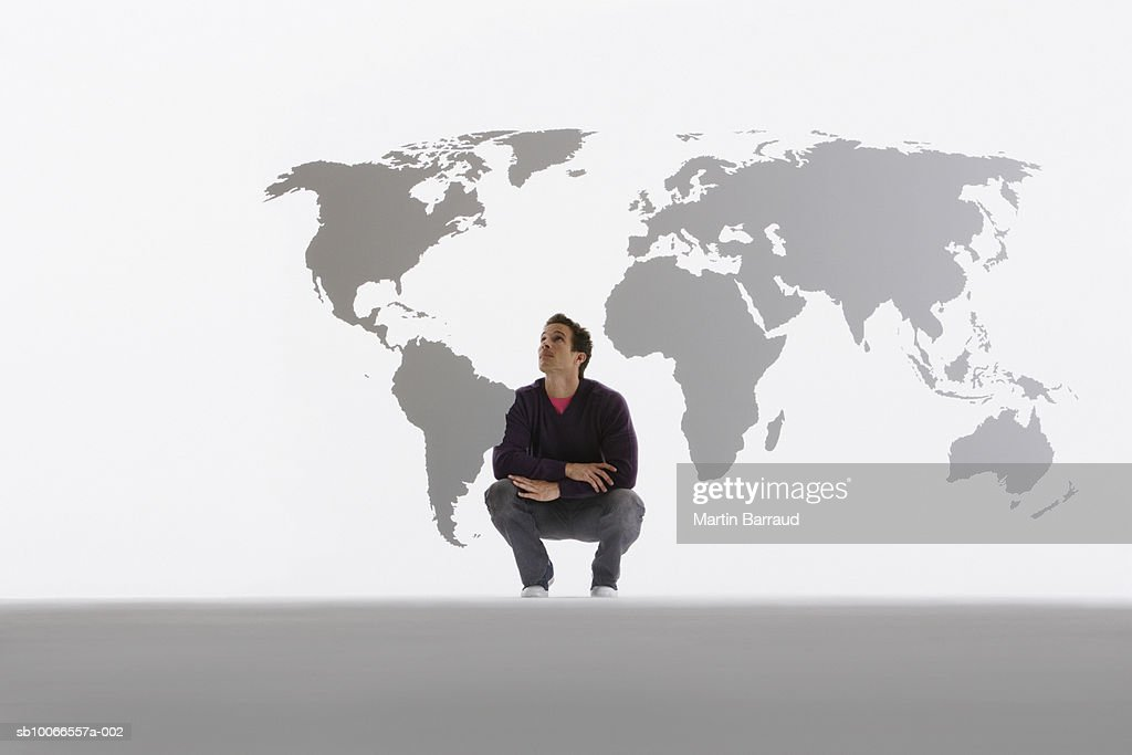 Man looking at map of world on clear acrylic sheet : Stock Photo