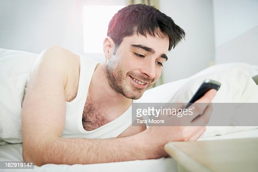 man looking at mobile phone in bed