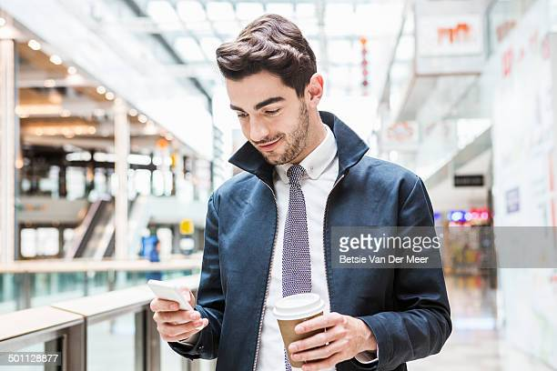 man looking at mobile phone in shopping centre.