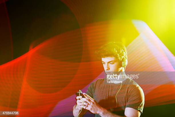 man looking at mobile wearing headphones