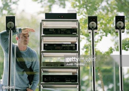 Man looking at music equipment through windows of electronics shop : Stock Photo