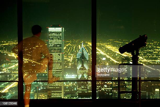 Man Looking at Nighttime Chicago From Building