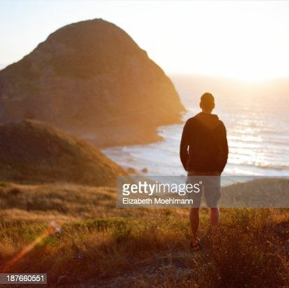 Man looking at ocean at sunset