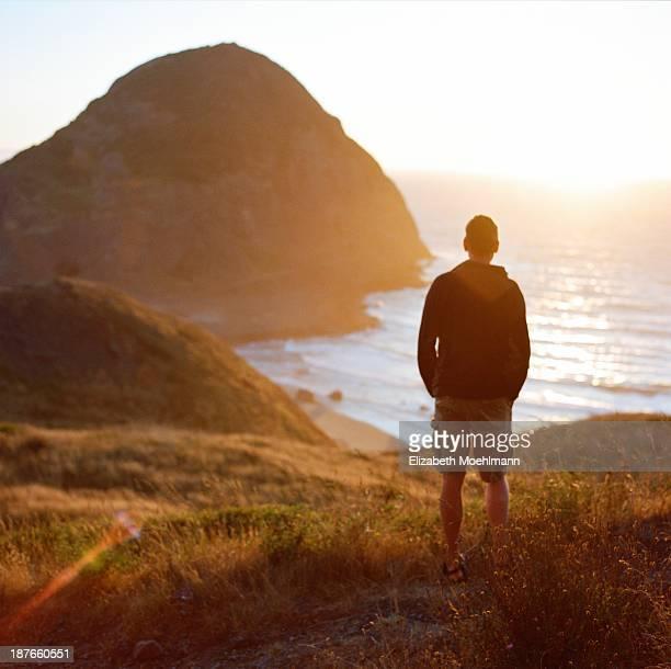 Man looking at ocean at sunset
