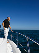 Man looking at ocean on bow of boat