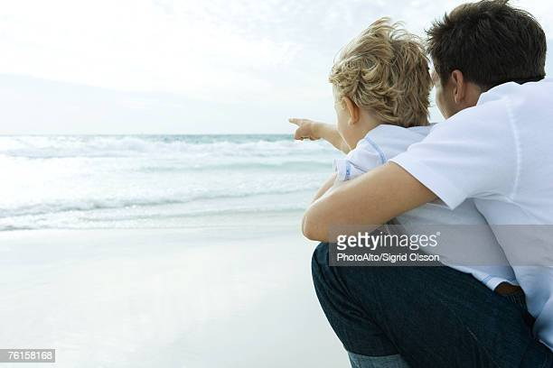 'Man looking at ocean with son, rear view'