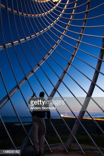 Man looking at Oresund bridge, linking Sweden and Denmark, through steel monument on the Swedish side. : Stock Photo