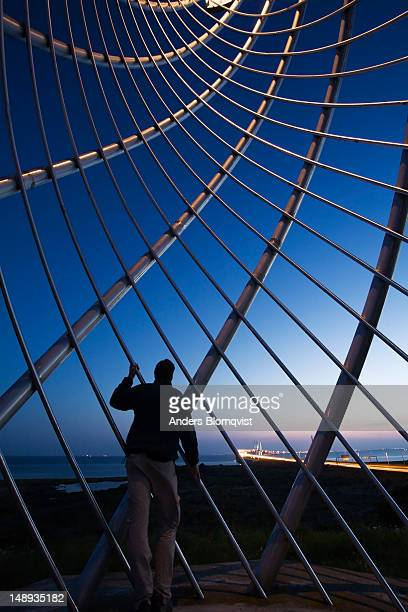 Man looking at Oresund bridge, linking Sweden and Denmark, through steel monument on the Swedish side.