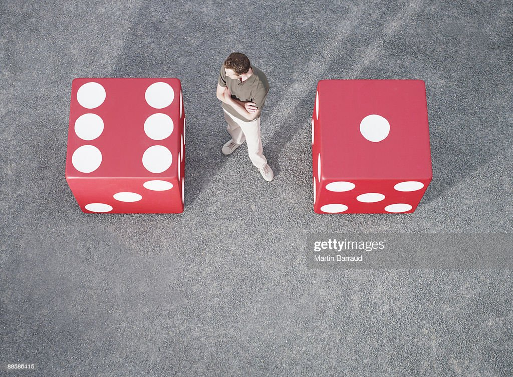Man looking at pair of giant dice : Stock Photo