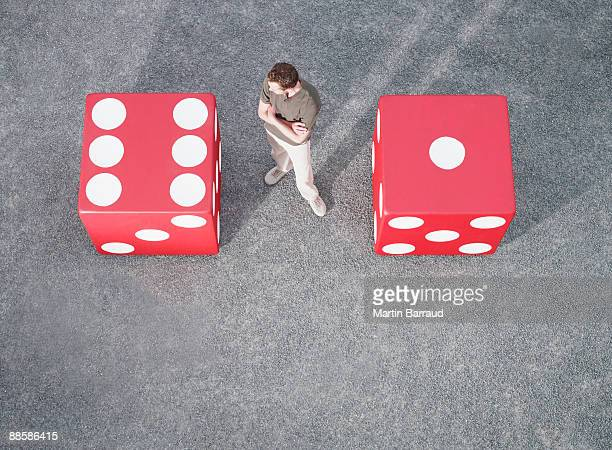 Man looking at pair of giant dice