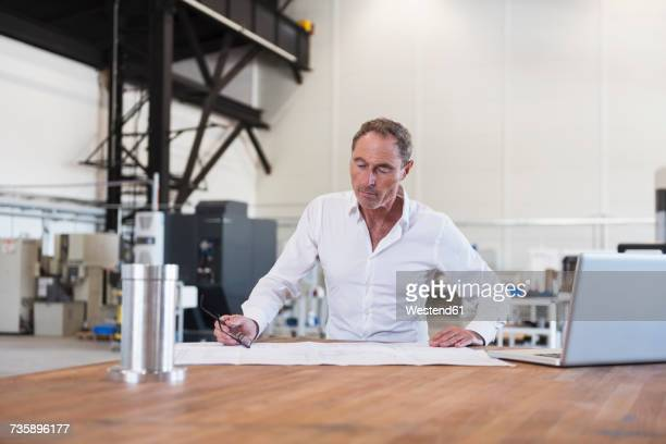 Man looking at plan on table in factory