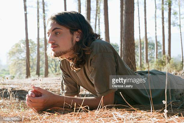 Man looking at plant on forest floor