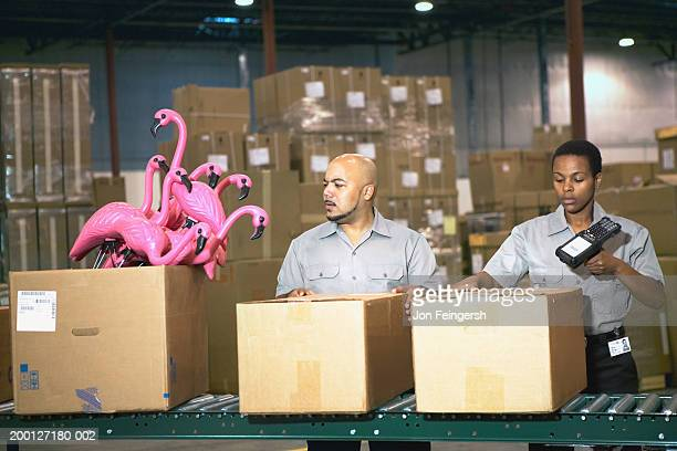 Man looking at plastic flamingos on conveyor belt, woman scanning box