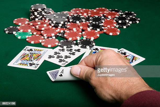 Man looking at playing cards near pile of poker chips