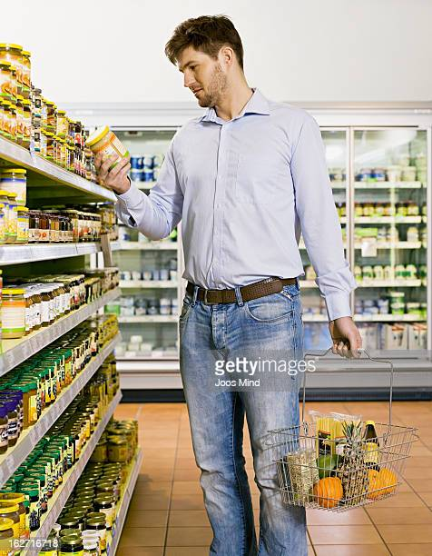 man looking at product packaging in supermarket