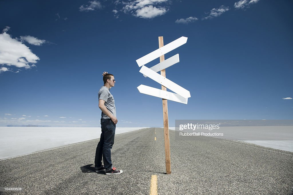 man looking at road signs on an open road