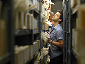 Man looking at rows of boxes in storage room, side view