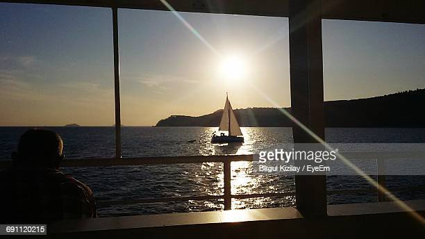 Man Looking At Sailboat Moving On River Against Sky During Sunset