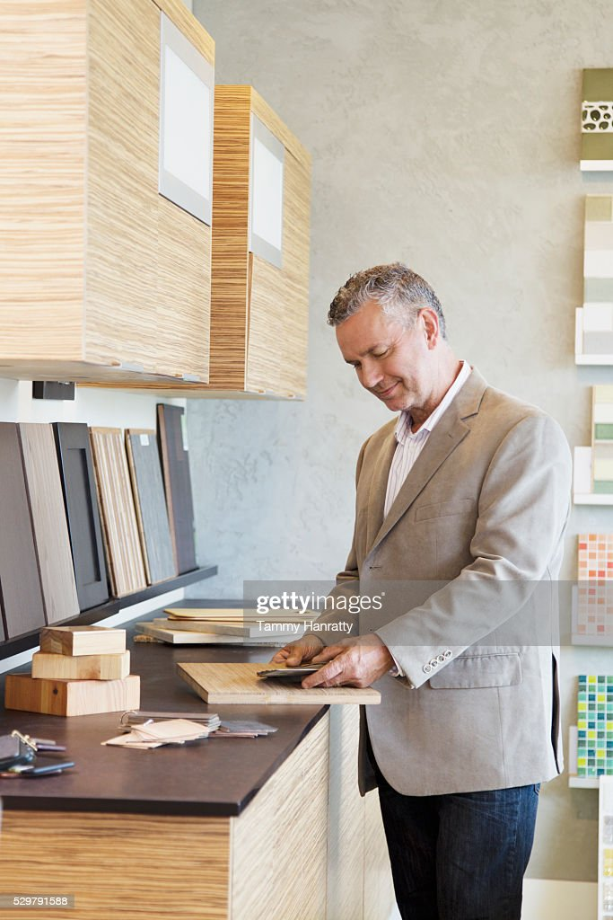 Man looking at samples of wood : Bildbanksbilder