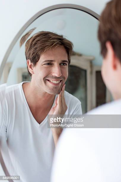 Man looking at self in mirror admiring facial stubble