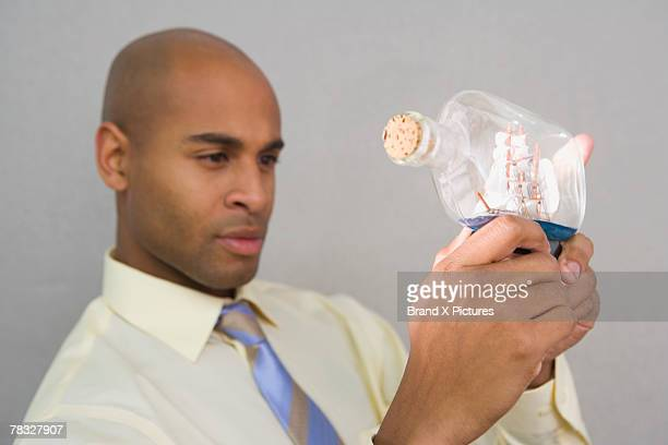 Man looking at ship in bottle
