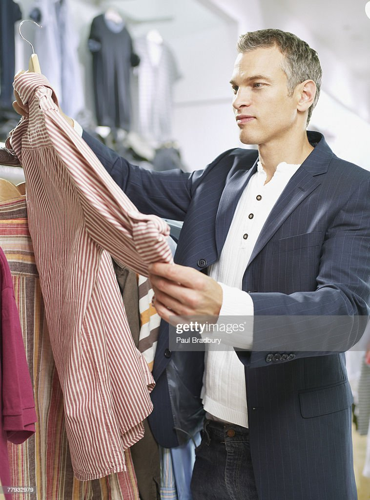 Man looking at shirt in store : Stock Photo
