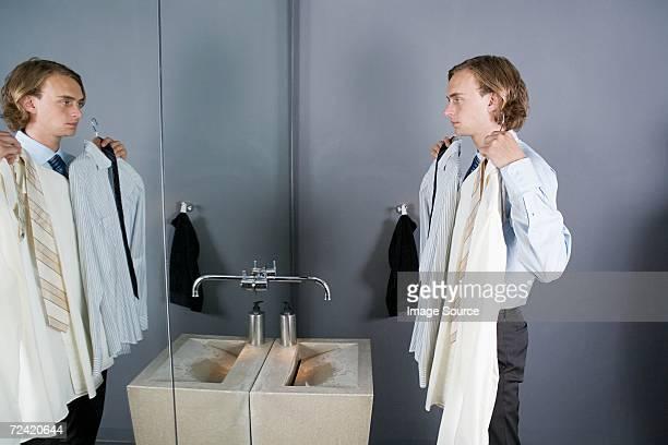 Camisas de hombre mirando en el espejo del baño