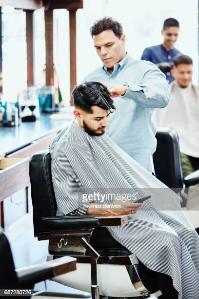 Man looking at smartphone while having hair cut in barber shop