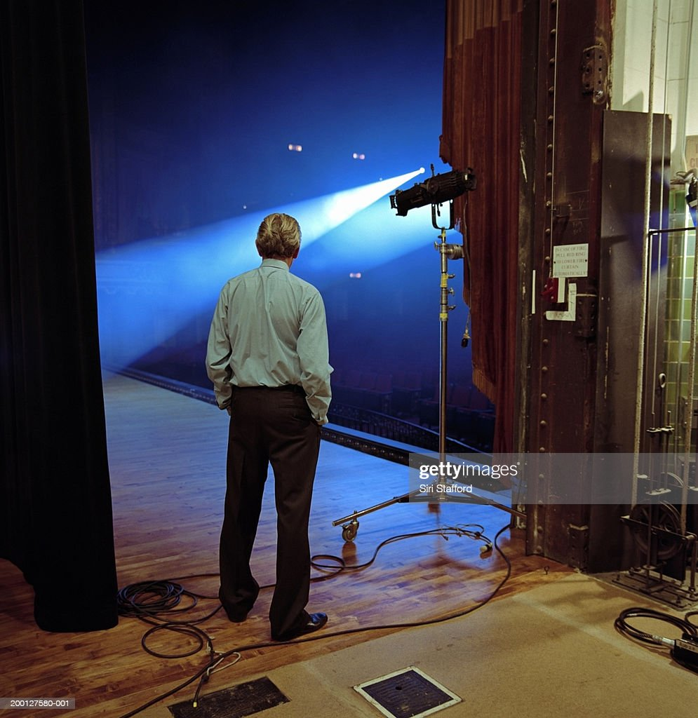 Man looking at spotlights on stage, rear view : Stock Photo