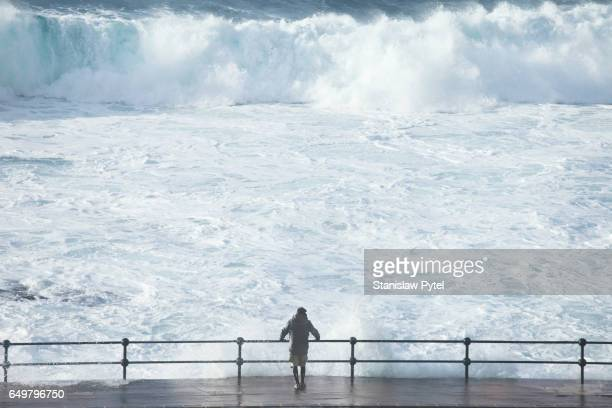 Man looking at stormy ocean