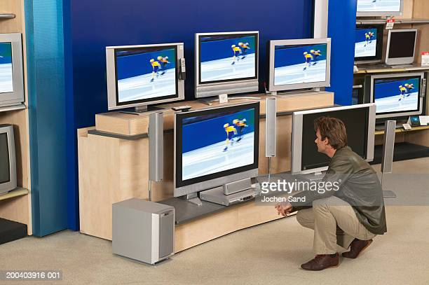 Man looking at television in shop