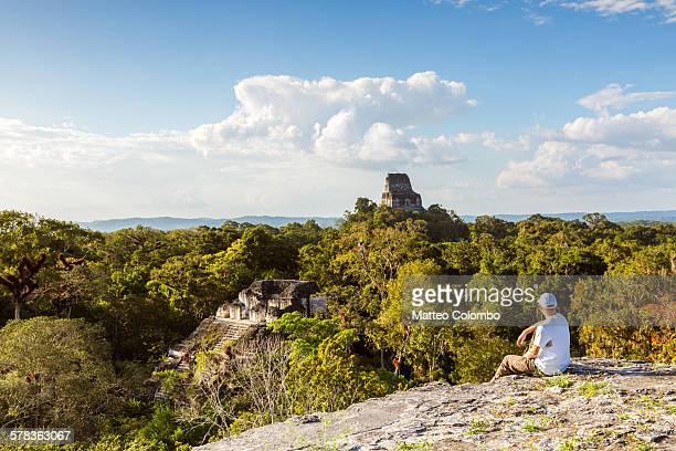 Man looking at temples in the forest, Guatemala
