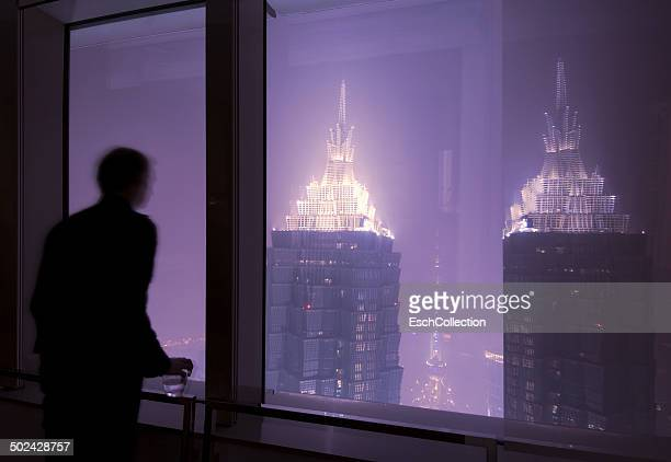 Man looking at the illuminated skyline of Shanghai