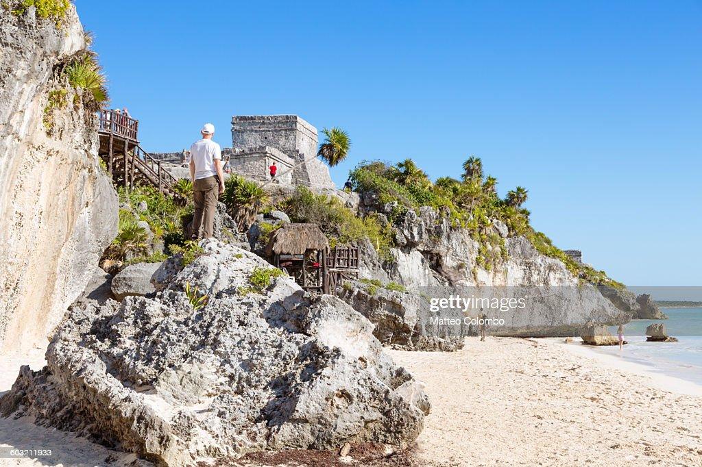 Man looking at the old ruins of Tulum, Mexico