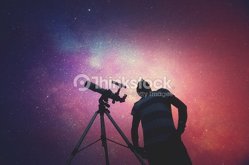 man looking at the stars with telescope beside him ストックフォト