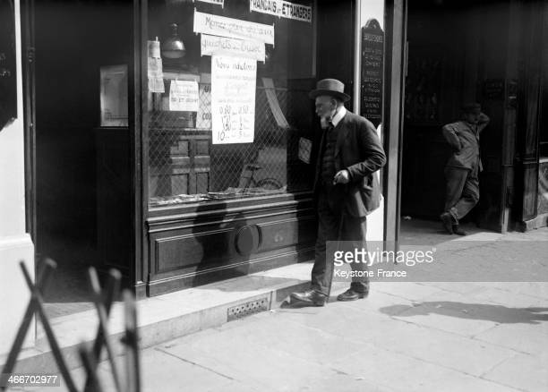 Man looking at the stock exchange prices at the window of a credit office circa 1920 in Paris France
