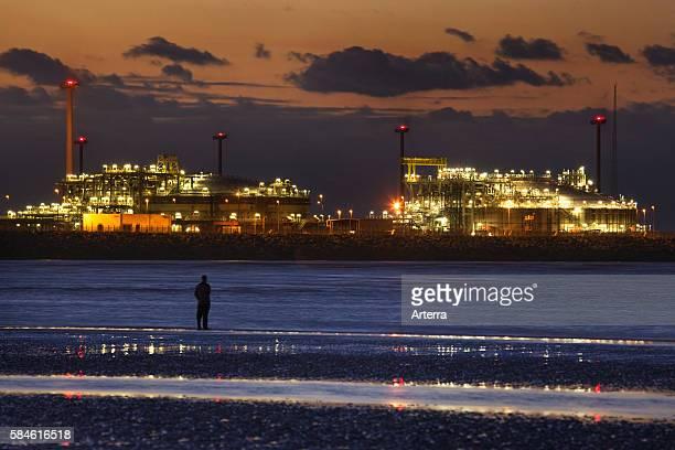 Man looking at the Zeebrugge North Sea port at sunset Belgium