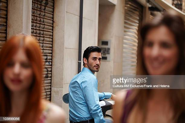Man looking at two women in street