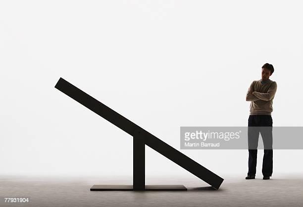 Man looking at unbalanced plank