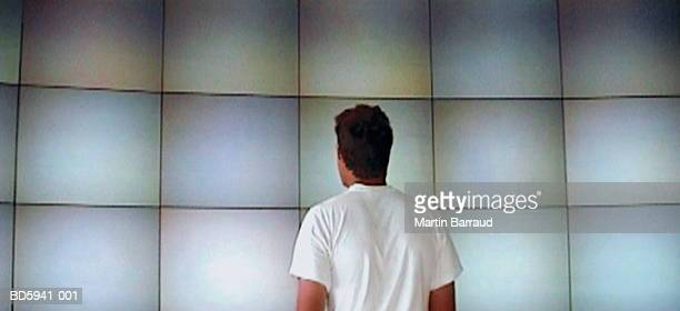 Man looking at wall of monitors, rear view (video still)