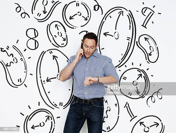 Man looking at watch surrounded by clocks