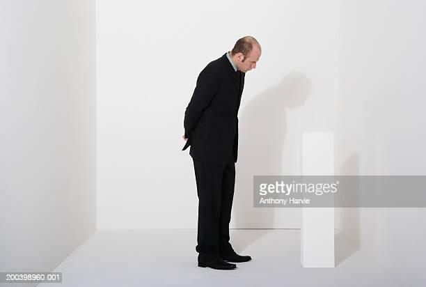 Man looking at white block
