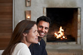 Man looking at woman by fireplace in resort