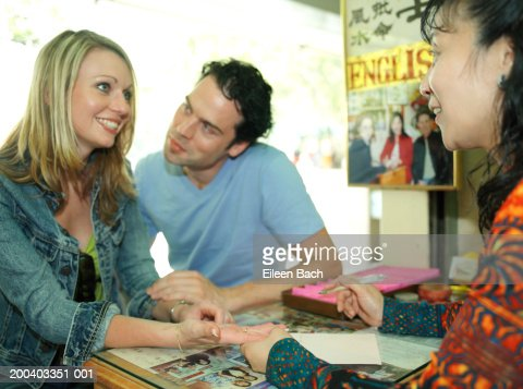Man looking at woman getting palm read, smiling