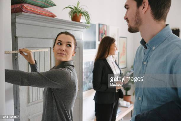Man looking at woman holding tape measure with female realtor in background