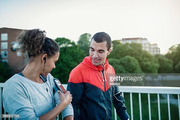 Man looking at woman using smart phone armband while walking at sidewalk