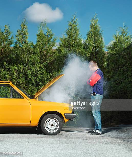 Man looking at yellow car with steam pouring from bonnet